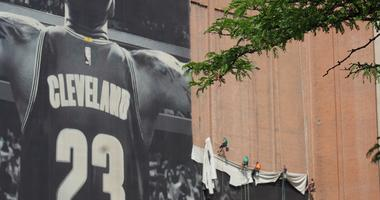 Workers remove Nike's 10-story tall LeBron James mural in downtown Cleveland on July 3, 2018.