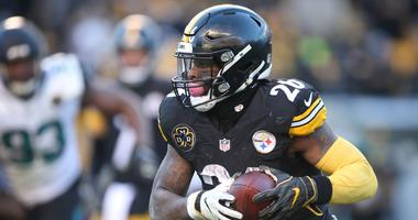 Jan 14, 2018; Pittsburgh, PA, USA; Pittsburgh Steelers running back Le'Veon Bell (26) rushes the ball against the Jacksonville Jaguars during the fourth quarter in the AFC Divisional Playoff game at Heinz Field. Jacksonville won 45-42. Mandatory Credit: C