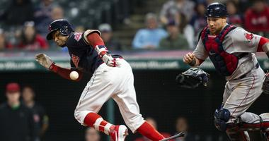 Sep 23, 2018; Cleveland, OH, USA; Cleveland Indians center fielder Rajai Davis (26) watches his sacrifice bunt bounce as Boston Red Sox catcher Christian Vazquez (7) chases it during the eleventh inning at Progressive Field.