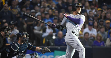 Oct 4, 2018; Milwaukee, WI, USA; Colorado Rockies outfielder Carlos Gonzalez hits a triple in the fifth inning against the Milwaukee Brewers in game one of the 2018 NLDS playoff baseball series at Miller Park. Mandatory Credit: Benny Sieu-USA TODAY Sports