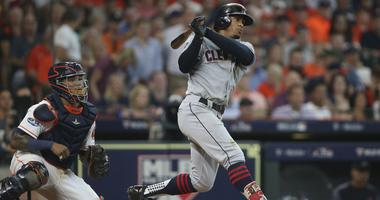 Cleveland Indians shortstop Francisco Lindor (12) hits a single in front of Houston Astros catcher Martin Maldonado (left) during the sixth inning in game one of the 2018 ALDS playoff baseball series at Minute Maid Park.