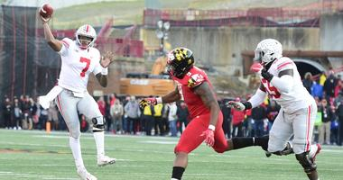 Ohio State Buckeyes quarterback Dwayne Haskins (7) throws as Ohio State Buckeyes defensive end Jashon Cornell (9) applies pressure during the fourth quarter at Capital One Field at Maryland Stadium.