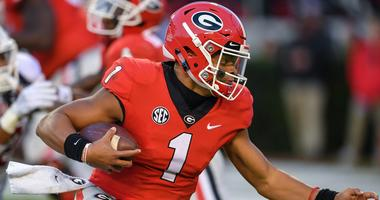 Georgia Bulldogs quarterback Justin Fields (1) runs for a touchdown against the Massachusetts Minutemen during the first half at Sanford Stadium.