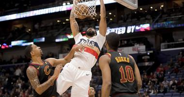 New Orleans Pelicans forward Anthony Davis (23) dunks over Cleveland Cavaliers guard Jordan Clarkson (8) and guard Alec Burks (10) during the first quarter at the Smoothie King Center.