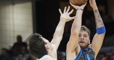 Dallas Mavericks forward Luka Doncic (77) shoots over the defense of Cleveland Cavaliers forward Cedi Osman (16) during the first half at Quicken Loans Arena.