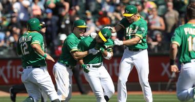 Oakland Athletics center fielder Ramon Laureano (22) is congratulated by teammates after driving in the winning run during the ninth inning against the Cleveland Indians at Oakland Coliseum.