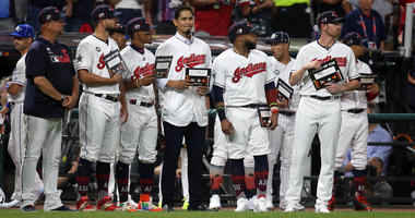 Jul 9, 2019; Cleveland, OH, USA; Cleveland Indians players stand with teammate Carlos Carrasco during the Stand Up For Cancer moment in the 2019 MLB All Star Game at Progressive Field. Mandatory Credit: Charles LeClaire-USA TODAY Sports