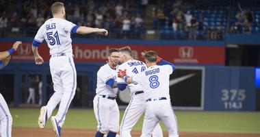 Toronto Blue Jays first baseman Justin Smoak (14) celebrates the win with relief pitcher Ken Giles (51) second baseman Cavan Biggio (8) infielder Eric Sogard (5) following the tenth inning against the Cleveland Indians at Rogers Centre.