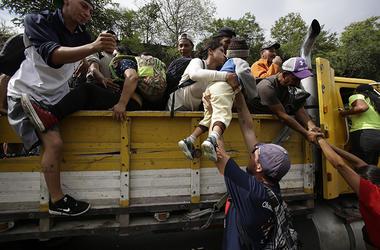 Migrantes hondureños con destino a la frontera de Estados Unidos suben a la parte trasera de un camión en Zacapa, Guatemala, el miércoles 17 de octubre de 2018.