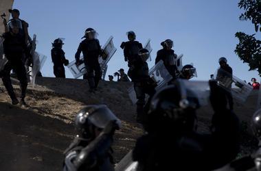 Policías mexicanos intentan impedir que un grupo de migrantes centroamericanos se desplace más allá del cruce fronterizo Chaparral en Tijuana, México, el domingo 25 de noviembre de 2018.