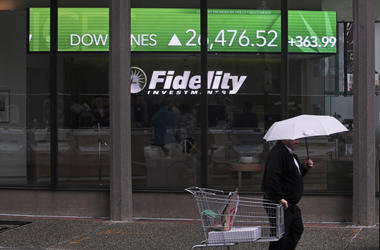 En esta foto del 18 de junio de 2019, un hombre con un carrito de supermercado pasa frente a una pizarra de la Bolsa que muestra una fuerte suba del índice Dow Jones.