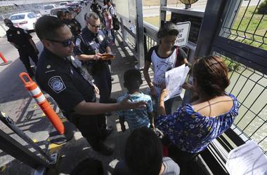 Foto de archivo del 17 de julio de 2019 de un agente fronterizo estadounidense verificando los documentos de migrantes antes de ser llevados a solicitar asilo en Estados Unidos, en el Puente Internacional 1 en Nuevo Laredo, México.