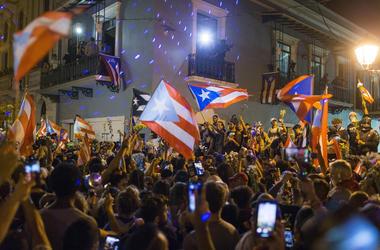 Gente celebrando ante la residencia oficial del gobernador de Puerto Rico, La Fortaleza, después de que el gobernador, Ricardo Rosselló, anunciara que dimitirá el 2 de agosto tras casi dos semanas de protestas, en San Juan, Puerto Rico, el jueves 25 de ju