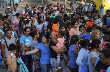 En esta fotografía del 30 de agosto de 2019, decenas de migrantes aguardan a recibir alimentos en un campamento cerca del Puente Nuevo Internacional en Matamoros.