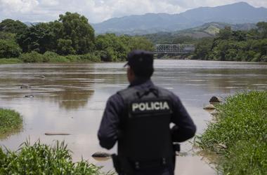 Un agente de la policía nacional salvadoreña observa el río La Paz en la frontera con Guatemala en La Hachadura, El Salvador, el jueves 12 de septiembre de 2019, como parte de un despliegue de 800 policías y soldados para patrullar los puntos ciegos a lo