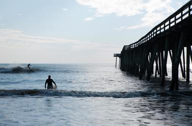 A man surfs near the Virginia Beach Fishing Pier