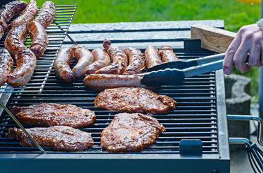 Steaks and sausages are grilled on the charcoal grill