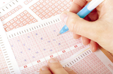 hand fills out lottery tickets with a pencil
