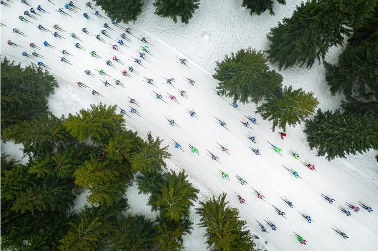 """The photo shows cross-country skiers during the Ski Racing Festival """"Bieg Piastów"""" competition in Poland. From the sky, the skiers look like a shoal of colorful fish floating among coral reefs."""