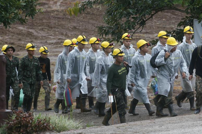 Rescatistas caminan hacia la entrada de un complejo de cuevas donde todavía hay cinco personas atrapadas, en el inicio de la tercera jornada de rescate, en Mae Sai, en la provincia de Chiang Rai, en el norte de Tailandia, el 10 de julio de 2018. (AP Foto/