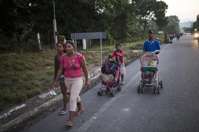 La familia Espinar camina por una carretera que une Pijijiapan con Arriaga, la próxima parada de la caravana de migrantes centroamericanos que viaja hacia la frontera con Estados Unidos, en México, el 26 de octubre de 2018. La familia procede de La Conce,