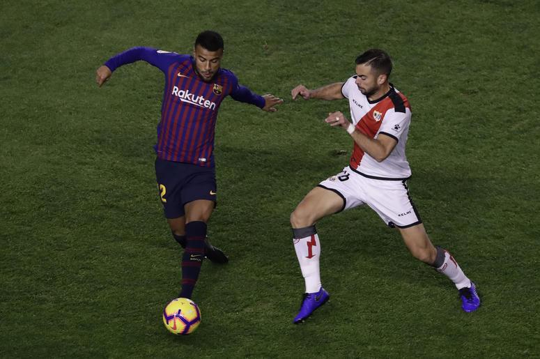 El brasilleño Rafinha, izquierda, del Barcelona, disputa el balón con Jordi Amat, del Rayo Vallecano, durante un juego de la Liga española en el estadio Vallecas de Madrid, España, el sábado 3 de noviembre de 2018.