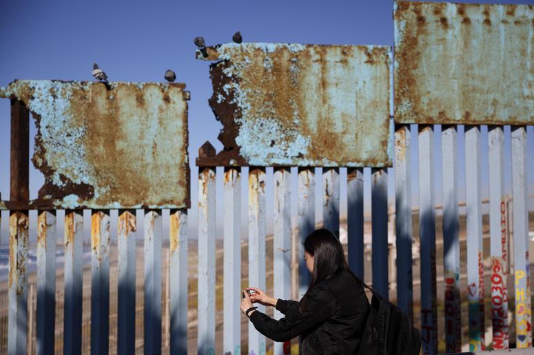 Una mujer toma fotos de un tramo herrumbrado del muro fronterizo entre EEUU y México cerca de Tijuana, México, el 7 de enero del 2019.