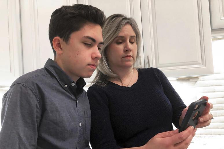 Fotografía de archivo del 31 de enero de 2019 de Gran Thompson y su madre, Michele, mientras ven un iPhone en la cocina de su casa en Tucson, Arizona.