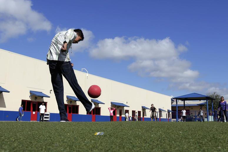 Fotografía de archivo del 10 de septiembre de 2014 de niños inmigrantes detenidos jugando a la pelota en el centro residencial del condado Karnes, un centro de detención para familias migrantes, en Karnes City, Texas.
