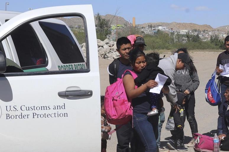 En esta imagen tomada de un video en abril de 2019, migrantes se entregan a agentes fronterizos en El Paso, Texas, después de cruzar hacia territorio estadounidense desde México.