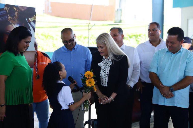 una estudiante entrega un jarrón con girasoles a la gobernadora de la isla Wanda Vázquez, durante su visita a la Escuela Ramón Marín Solá, en Guaynabo, Puerto Rico, el lunes 12 de agosto de 2019.