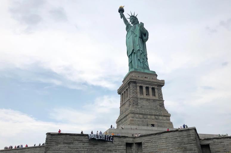 En esta fotografía difundida por el grupo Rise and Resist, varios manifestantes despliegan una carta que pide abolir el Servicio de Control de Inmigración y Aduanas de Estados Unidos (ICE por sus siglas en inglés) en la base de la Estatua de la Libertad.