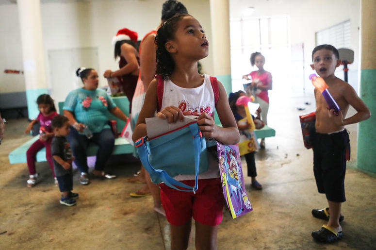 TOA BAJA, PUERTO RICO - DECEMBER 25: Janellise Rivera (C), whose family lost their home in Hurricane Maria, waits to receive a Christmas present from a church group in a shelter for Hurricane Maria victims on December 25, 2017 in Toa Baja, Puerto Rico. 12