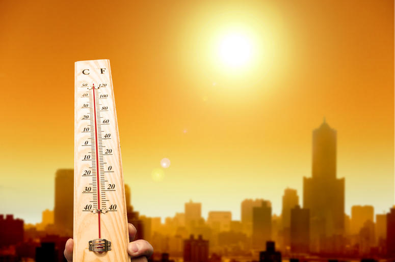 Thermometer shows high temperature with city in background