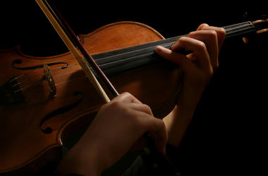 Violin is in the hands of professional violinist. Details of violin playing isolated on