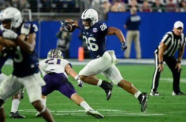 Penn State Nittany Lions running back Saquon Barkley (26) dodges a tackle by Washington Huskies defensive back Taylor Rapp (21) during the second half during the 2017 Fiesta Bowl at University of Phoenix Stadium.