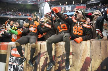 Cleveland Browns linebacker Xavier Woodson-Luster (56) and wide receiver Breshad Perriman (19) celebrate with fans after the Browns beat the Cincinnati Bengals at FirstEnergy Stadium.
