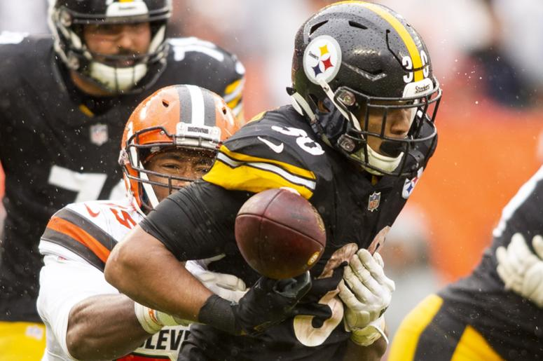 Cleveland Browns defensive end Myles Garrett (95) forces a fumble by Pittsburgh Steelers running back James Conner (30) during the fourth quarter at FirstEnergy Stadium.