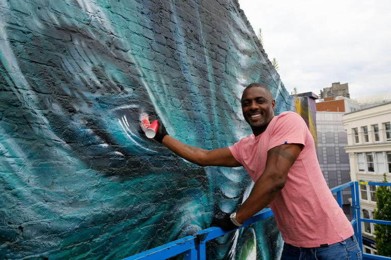 """Idris Elba paints in the eye of his character """"Krall"""" during the unveiling of a Star Trek Beyond mural by artist Jim Vision in Clerkenwell, London"""