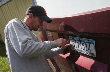 Man removing New York license plate