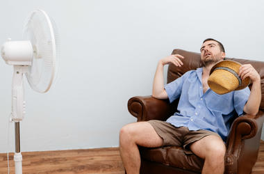 hot day man in chair with fan
