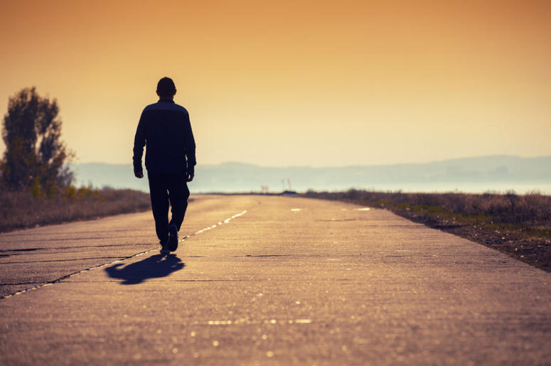 man walking on country road