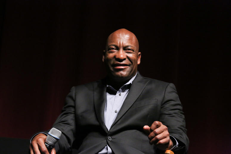 "John Singleton sits in a chair smiling at a discussion at the ""Spotlight On Screenwriting: Boyz n the Hood 25th Anniversary Screening With John Singleton And Walter Mosley"" presented by The Academy Of Motion Picture Arts And Sciences."