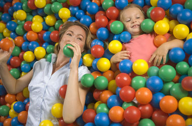 High angle view of a girl with a mid adult woman lying in a ball pool
