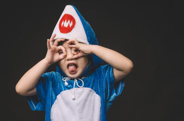 Child with baby shark costume in studio portrait