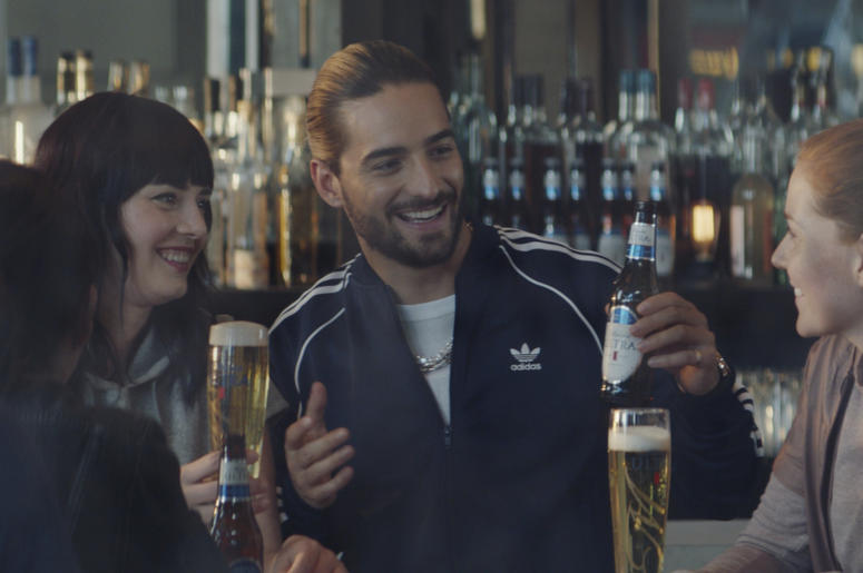 This undated image provided by Michelob ULTRA shows a scene from the company's 2019 Super Bowl NFL football spot featuring Maluma, center. In the ad for Michelob Ultra, a robot beats humans at different sports like running and spinning. But then he looks