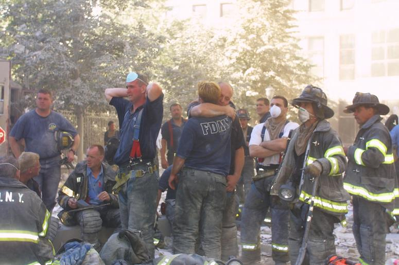 New York City firefighters hug each other during rescue operations at the World Trade Center after two hijacked planes crashed into the Twin Towers September 11, 2001 in New York. (Photo by Ron Agam/Getty Images)