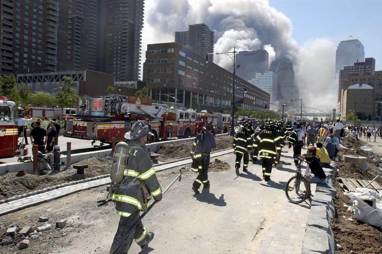 Fireman heading south on the West Side Highway towards the remains of the World Trade Center where smoke continued hours after the colapse. Streets of lower Manhattan with fireman, police, and rescue crews after the colapse of the World Trade Center after