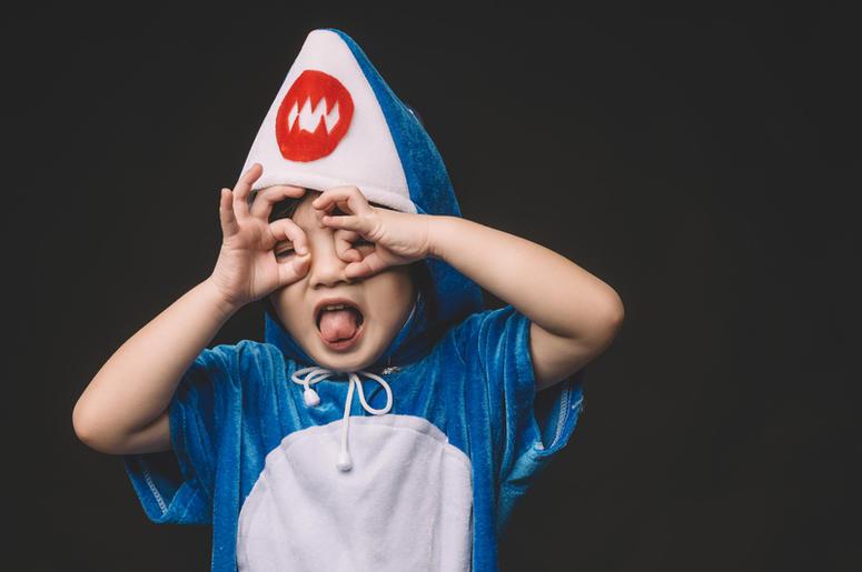 Child with baby shark costume in studio portrait