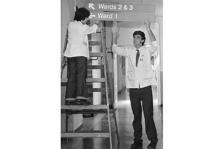 English actor Peter Mayhew (right) helps put up signs to the wards at King's College Hospital, where he works as an orderly, 3rd June 1977. Mayhew, who is 7'3'' tall, gained fame as the Wookiee Chewbacca in George Lucas' 'Star Wars' films. (Photo by Colin